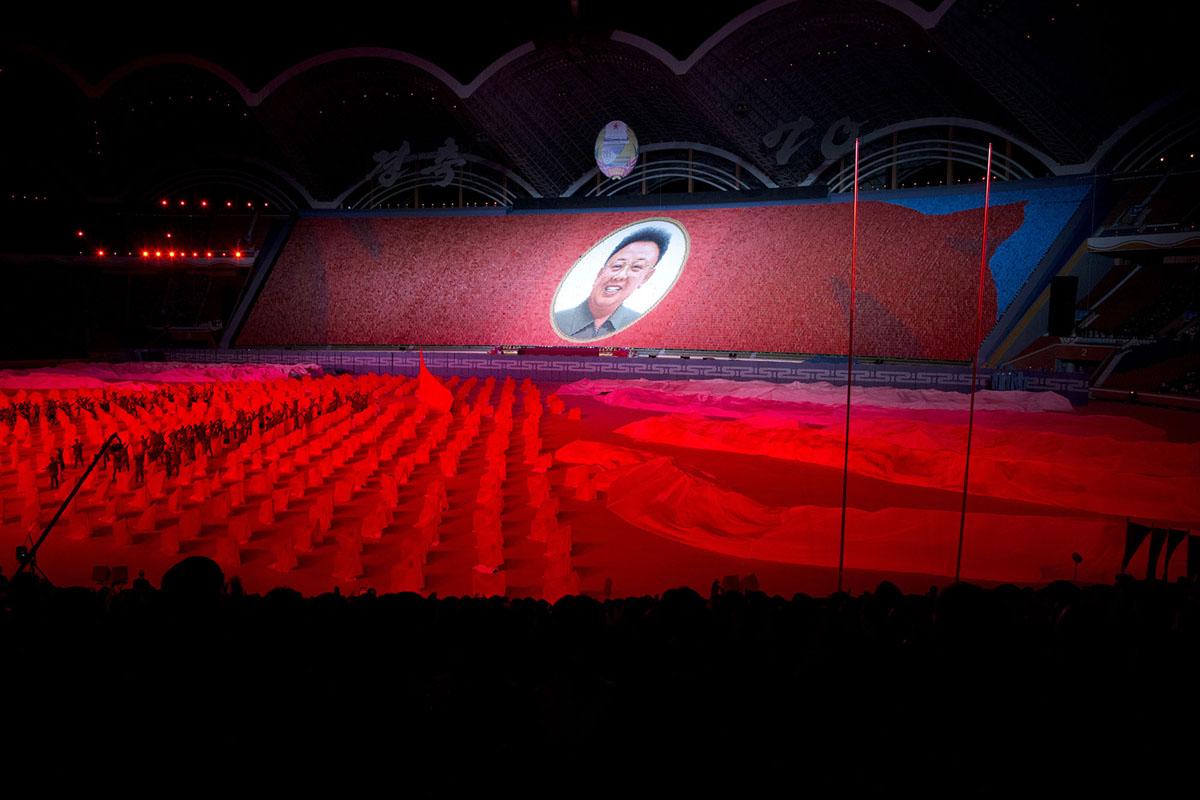 Прапори на північнокорейському стадіоні.  На трибуні - портрет Кім Ір Сена.