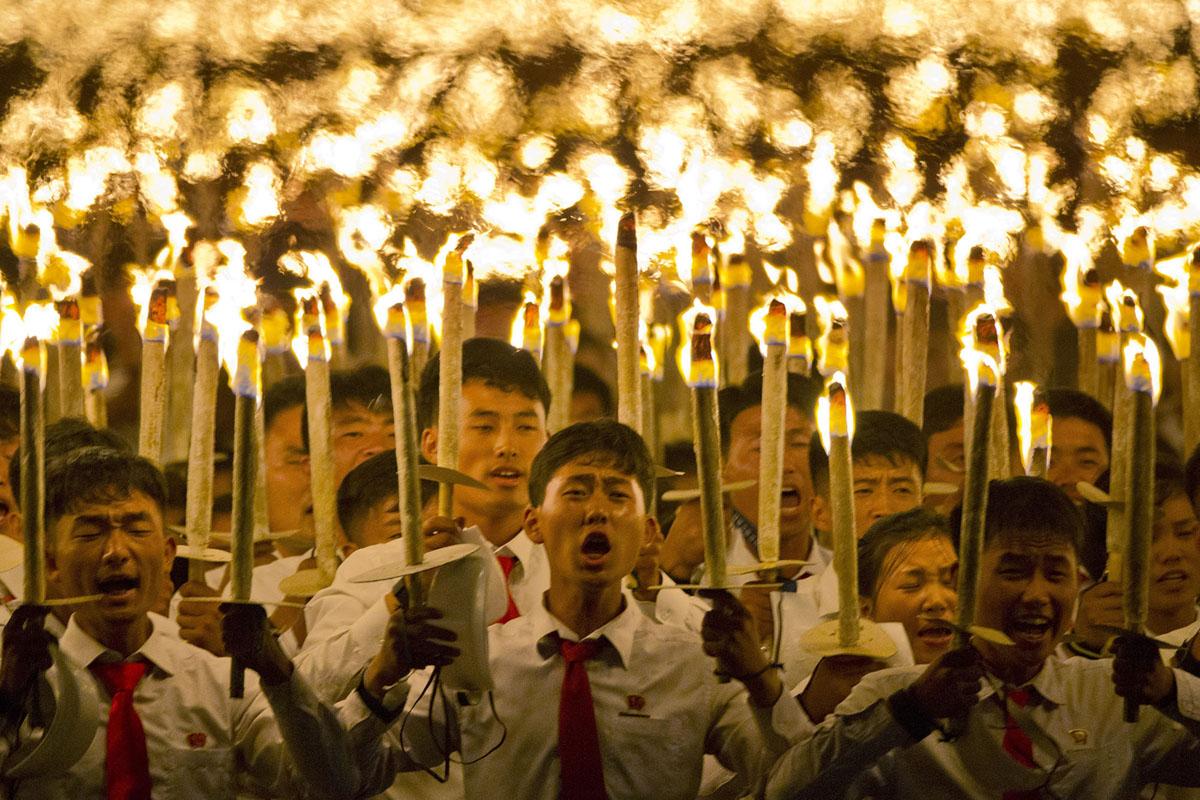 Північнокорейські студенти беруть участь в факельній ході.